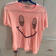 WILDFOX OVERSIZED FIT ICECREAM SMILEY TEE Size xs but it's oversized so it will fit xs-med easily! Super soft and very light (semi sheer so wear a cute bra!). Pale pink (ballet pink really cute!) one small area next to,the right ice cream cone that didn't wash out. Not sure what happened but I wanted to disclose that minor spot! See the last photo to see what I meant. It's not noticeable when wearing, but I wanted to be up front!✌️ Wildfox Tops Tees - Short Sleeve
