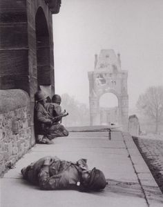 US soldiers attempting to stay out of a sniper's sight after a comrade was hit. Worms, Germany March 1945.