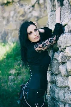 Sexy alternative model and dark goddess Kali Noir Diamond, showing off her sensual curves against an ancient stone wall.