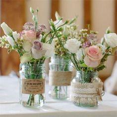 Centros de mesa, flores en tonos rositas bajitos y blancos.