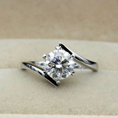 The ring features a 1 carat round cut center stone set on a six V peg head…