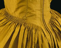 Detail robe à l'Anglaise in a polonaise style, England, c. 1774. Gold silk taffeta, lined with linen. The back is in 'English' style, with an extra double fold at the centre back. The skirt is organ pleated onto a concave waist seam. There is a self covered button at each side back seam to which the pink cords inside the dress can be attached forming a polonaise.