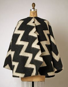 Coat. Fall/winter 1996-1997. American. This coat was designed by Geoffrey Beene, who was an American designer. It is made out of wool, and silk. This coat looks futuristic with the zig-zag design on it. It looks like something people would wear today. When I think of the 90s, I think more of the grunge look, but this could definitely be paired to look grunge. The Metropolitan Museum of Art.