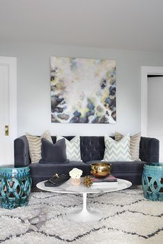 Stunning living room features a yellow and gray abstract art piece which hangs over a navy velvet tufted sofa with high back adorned with gray zebra pillows and aqua chevron pillows facing an Saarinen Oval Coffee Table and a pair of turquoise rope stools atop a Beni Ourain Rug.