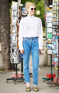 A feminine Victorian white high neck blouse is worn with high-waisted jeans, loafers, and round sunglasses