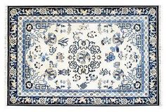 Vintage hand-knotted Chinese rug with blue floral motifs on a white field.
