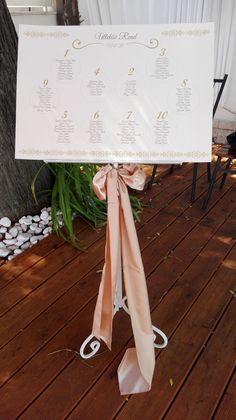 Esküvői dekoráció - ültetési rend és bézs masnival díszített ültetési rend tartó az Udvarház Étteremben.