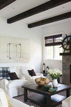 Nautical White Living Room    Reclaimed materials and vintage art add interest.    To achieve a historical feel and balance the dark flooring in this room, reclaimed ceiling beams were painted black. A painting of an old boat lift adds to the vintage vibe of the space.