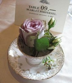 Wedding Flowers Flower arrangements don't have to be large to be decorative - pretty vintage china with a single rose and buds adds a light unique style touch to the table setting.