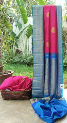 This kanchivaram silk is in magenta with gold zari bhuttas all over. The border and pallu complement the sari well in cobalt blue with intricately woven gold zari making it absolutely enigmatic
