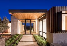 This modern house features large overhanging, wood lined roof sections that cover walkways and connect the various areas of the house. #ModernHouse #Roof #WoodOverhang #Front Door #Landscaping