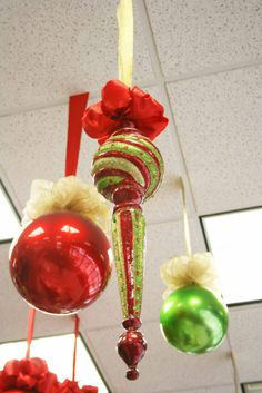 christmas ornaments hanging from ceiling in red gold and green