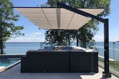 ShadeFX Top Projects for 2020. #1. Freestanding Retractable Canopy, Lake Simcoe. The backyard of a beautiful home in Brechin, Ontario was redesigned to take full advantage of its impressive waterfront views. #retractableshade #outdoorliving #retractableawning #retractablecanopy #retractablepergola #sunprotection #topprojects #poolsideshade #backyardretreat #rainprotection #waterproofcanopy #backyardrenovations #curbappeal #backyardinspiration #umbrella #landscapedesign #patiorenovations Shade Structure, Backyard Pavilion, Backyard Retreat, Retractable Canopy, Backyard Renovations, Lakefront Homes, Shades, Outdoor Seating, Showroom