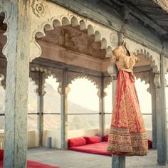 Coral red lehenga with gold blouse shot against the gorgeous arches of devigarh palace . Outfit by #frontierraas
