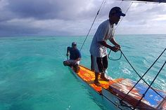 Marshalhese men steering a traditional outrigger canoe, Ailuk atoll, Marshall…