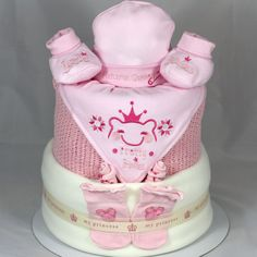 Super cute Little Princess 2 Tier Nappy Cake, featuring a gorgeous Princess or Prince Hat, Bootee and Bandana set. All our nappy cakes are gift wrapped in celophane and decorated with colour cordinated pull bow and curlng ribbon with a a content card and handmade gift card.