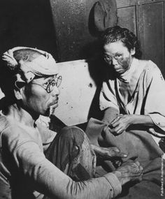 Victims of the atomic blast sit in a makeshift hospital in a damaged bank building in the centre of Hiroshima.