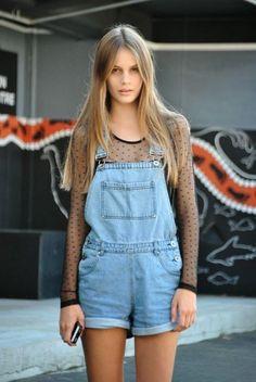 Denim short overalls over sheer blouse.