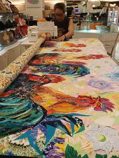 "Danny Amazonas working on his quilt ""Rooster Party"" - photo from Mania for Quilts blog;  He makes work ""easier by fusing all his fabric with fusible web and cut to desired size and shapes as he pastes or paints as he calls it."""