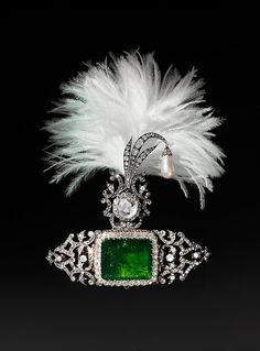 Turban Ornament and Brooch (sarpesh) Object Name: Turban Ornament Date: Turban ornament: ca. 1900; clip on reverse made by Cartier Paris, 2012 Geography: India Medium: Gold and silver, set with emerald, diamonds and hanging pearl Dimensions: H. 4 5/8 in. (11.7 cm) W. 5 1/8 in. (12.8 cm) Classification: Jewelry Credit Line: The Al-Thani Collection