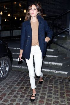 Alexa Chung in a camel sweater, white jeans, navy coat and strapped ballet flats