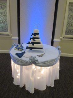 Wedding Cake Table With Lighting And Silver Swag Around. #caprottiscatering  #capriottispalazzo #wedding #weddingcake