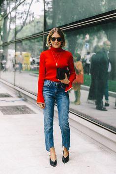 Un jean brut asymétrique avec un col roulé rouge et des bijoux dorés