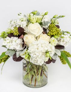 Divine Whites - A classic collection of all whites and creams designed in a clear cylinder vase. This simple, elegant arrangement makes for a timeless gift for any occasion.