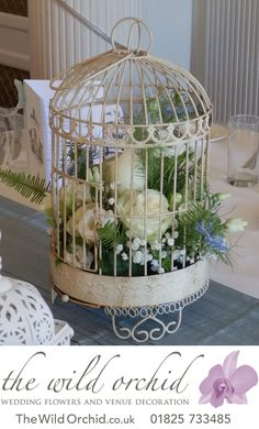 """Birdcages remain popular in 2014. Here one is filled beautiful ivory Avalanche roses, white double lisianthus, ivory freesia, white gypsophilia and touches of blue Nigella """"love in the mist"""". A pillar candle is nestled in amongst the flowers."""