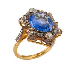 Antique Sapphire Diamond Ring image 2. Circa 1900, twinkle, twinkle... shaped like a star, the design features a very nice elongated octagonal shaped blue sapphire weighing approximately 4.61 carats, the color sometimes referred to as cornflower blue, within a silver-topped border set with old mine-cut diamonds, the shoulders set with similarly cut diamonds, mounted in 18 karat yellow gold and silver topped. c 1900