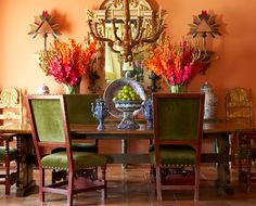 In the dining room, a 17th-century Spanish mirror complements an Italian chandelier from the Pittet Company. Pottery by Gorky Gonzalez hails from Guanajuato, Mexico. Gold Majorcan chairs are from Orion. Flowers are by Arrangements by Mary Parks. | Jane and Kevin McGarry's Fort Worth Residence | D Magazine
