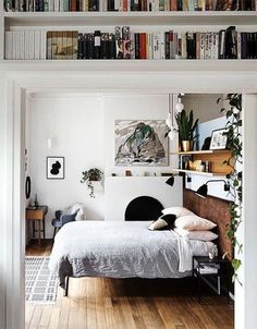boho minimal bedroom with bookshelves above the doorframe | an eclectic mix of books, art and plants creates a homey and cosy feel | simple white and grey bedlinen | Get the look with a Bemz bedspread
