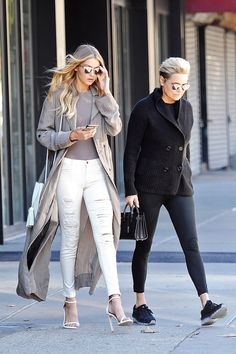 Gigi Hadid wearing a neutral trench coat and ripped white skinny jeans with strappy sandals and mirrored sunglasses.