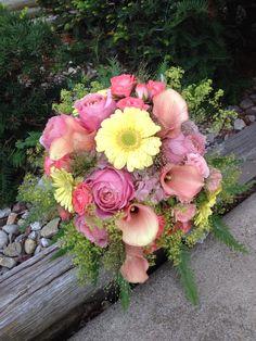 Shades yellow, coral & pink bridal bouquet. Calla lilies, mini gerbera daisies, garden roses, spray roses & explosion grass.