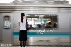 Foto stock : Young woman standing on station platform, rear view (blurred motion)
