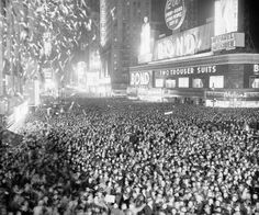 Rain ushered in 1938, but that didn't deter thousands of people from filling Times Square, New York. This view looks south across West Forty-Fourth street with the old New York Times building in the background.