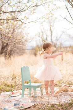 2 year old photo idea. Spring photo shoot. Apple orchard in bloom. Vintage styled family shoot, child antique chair. Toddler Dancing #BellaFotiaDesign