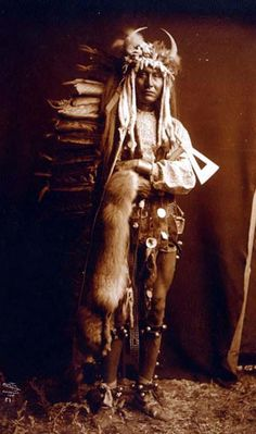 Iron Breast. It was created in 1900 by Edward S. Curtis.    The photo illustrates Iron Breast, full-length portrait of a Piegan man, standing, wearing war bonnet, holding tomahawk and animal pelt draped over his arm.