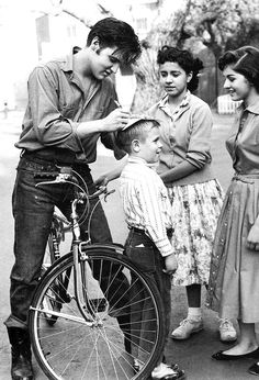 Elvis Presley stops to sign autographs for fans in Germany, 1959.
