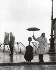 Musician waiting in the rain for a bus.Paris,France.