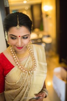 South Indian bride. Gold Indian bridal jewelry.Temple jewelry. Jhumkis. Cream silk kanchipuram sari.Braid with fresh jasmine flowers. Tamil bride. Telugu bride. Kannada bride. Hindu bride. Malayalee bride.Kerala bride.South Indian wedding.