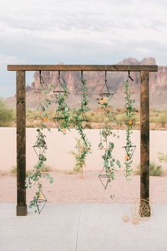 Geometric desert wedding arbor with hanging greenery and color-coordinated flowers scattered throughout.