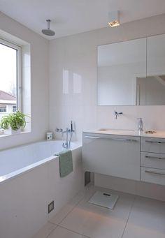 Det helhvite baderommet er minimalistisk med rene linjer og blanke overflater. Her kan du velge om du vil ta deg et avslappende bad, eller om du vil la vannet strømme fra dusjhodet i taket og ta en kjapp dusj.