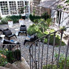 Des graviers, des petites touffes de verdures et de simples fauteuils design ikea, un jardin plein de charme !