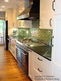 Green back splash with butchers block counter tops and white cabinets