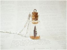 Ok, so it is a snowglobe made with a tiny bottle and it has a feather inside. Oh, and it is a necklace! Too sweet!