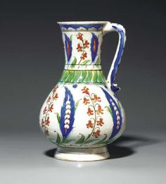 AN IZNIK POTTERY JUG  OTTOMAN TURKEY, CIRCA 1590  Of baluster form on short foot rising to a flaring trumpet mouth & with simple loop handle, white body decorated in cobalt-blue, bole-red, black & green, with alternating large blue saz leaves & red hyacinth sprays each rising from a tuft of leaves, neck with similar but reduced design, a ring of stylized marbling at the base, a register of green overlapping lappets & a smaller white band at the waist...  9½in.  high