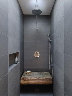 Grey and raw wood shower. Very Scandinavian style to mix two contrasting elements like this and let the natural material shine.