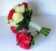 Hot pink and ivory rose bouquets for a bride and her bridesmaid with pretty lace ties