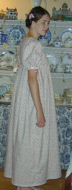 This Regency style day dress is classically high waisted. It has a scooped neckline and full gathered sleeves. There are satin ribbon drawstrings in the waist and sleeves. The skirt has fuller pleating in the back and a flatter front panel. This dress can be made in any cotton calico found on this page http://www.princessandpuddles.com/regency-cotton-calicos.html.